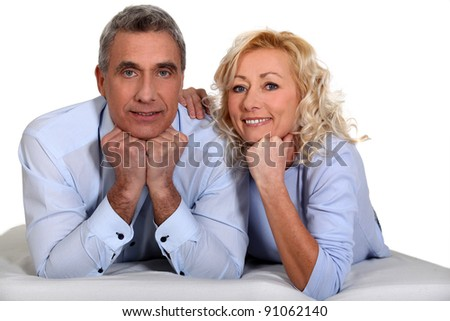 Middle-aged couple laying together