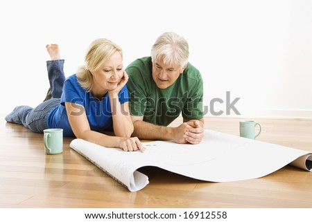 Middle-aged couple lying on floor looking at architectural blueprints together. Photo stock ©