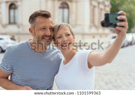 Middle-aged couple posing for a selfie on their mobile phone in town standing close together smiling at the camera #1101599363