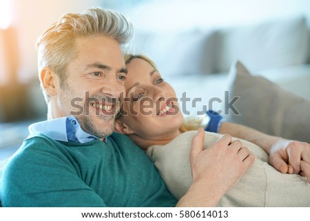 Middle-aged couple relaxing together in sofa