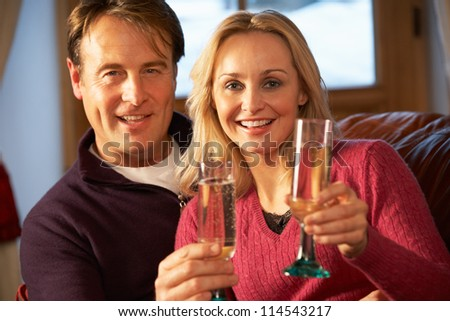 Middle Aged Couple Sitting On Sofa With Glasses Of Champagne Stock photo ©