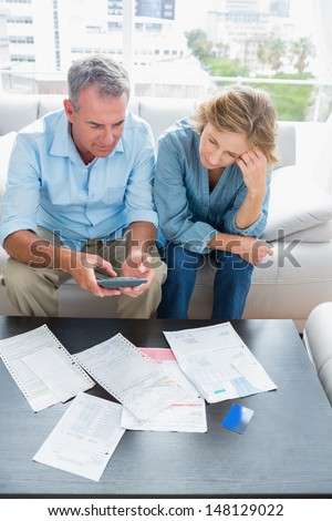 Middle aged couple sitting on their couch paying their bills at home in the living room