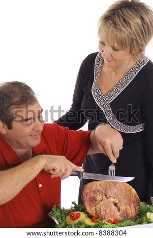 middle aged couple slicing ham