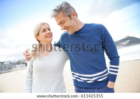 Middle-aged couple walking together on a sandy beach
