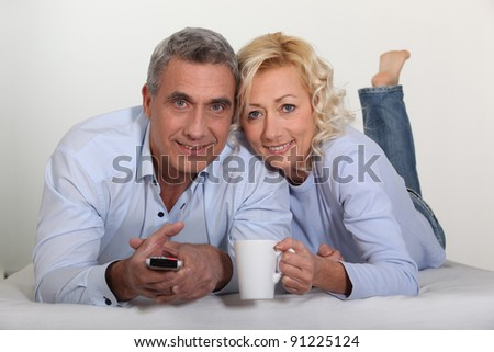 Middle-aged couple watching television - stock photo