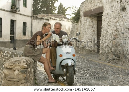 Middle aged couple with scooter reading map on street, Granada; Spain