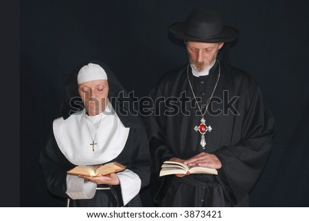 Middle aged devout nun and priest in deep thoughts, praying.  Religion, christianity, lifestyle concept