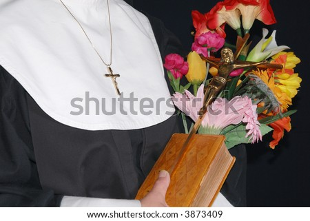 Middle aged devout nun  holding on to bible, cross and flowers.  Religion, christianity, lifestyle concept