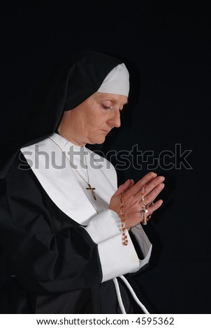 Middle aged devout nun in deep thoughts, praying.  Religion, christianity, lifestyle concept