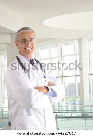 Middle aged doctor wearing lab coat and with arms crossed in modern medical facility