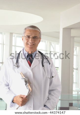 Middle aged doctor wearing lab coat holding a Clip Board in modern medical facility