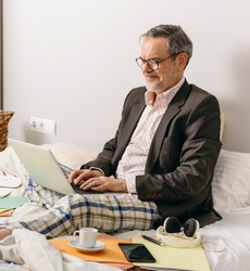 Middle-aged executive participating in a business meeting via videoconference from the office mounted on his home bed