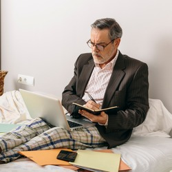 Middle-aged executive taking notes in a work video conference from the office mounted on his home bed