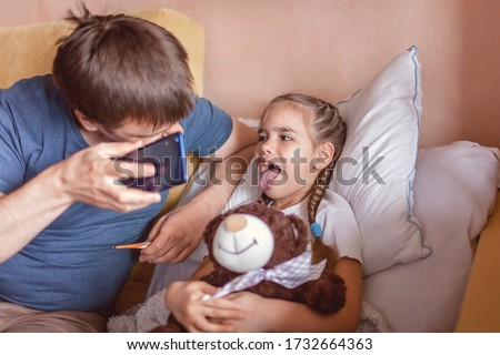 Middle-aged father looking at screen of smartphone and consulting with a doctor online at home, telehealth services during lockdown, distant video call, modern tech healthcare application