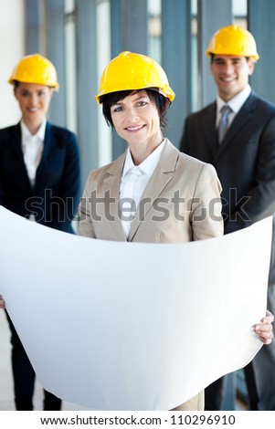 middle aged female architect holding blue print in front of colleagues