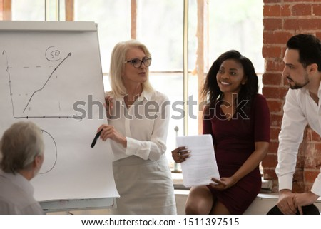 Middle-aged female company ceo make presentation provide information sales statistics in graphs use flip chart multi-racial colleagues listen business trainer got knowledge, corporate training concept