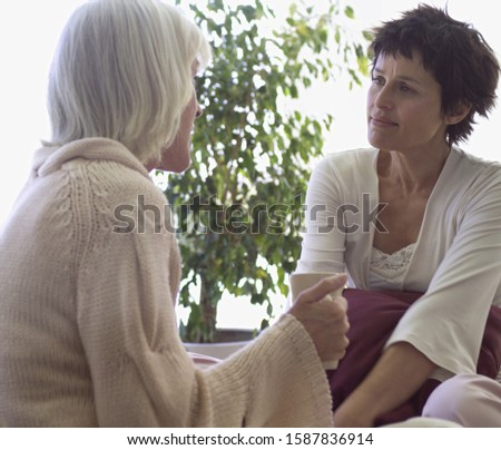 Photo of Middle-aged female couple talking on sofa