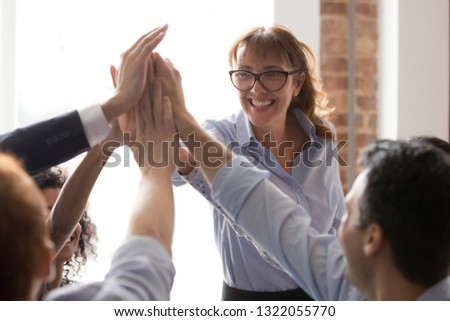 Middle aged female mentor coach teacher give high five to employees students group, team members promise unity support in teamwork, engaged in motivational training celebrate business success concept