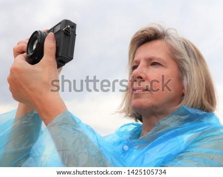 middle aged female photographer taking photos outdoors.senior female amateur photographer taking photos.