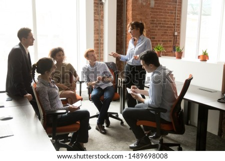 Middle aged female team leader or boss hold casual group meeting talking with employees brainstorming in shared office, manager speak sharing ideas at informal briefing with coworkers