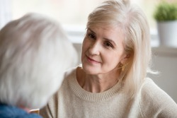 Middle aged female with blonde hair looking at grey haired male, close up focus of woman face. Attentive wife listens her beloved husband sitting together at home spending enjoying free time together