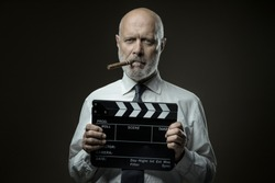 Middle-aged film director holding a clapperboard, cinematography and film industry concept