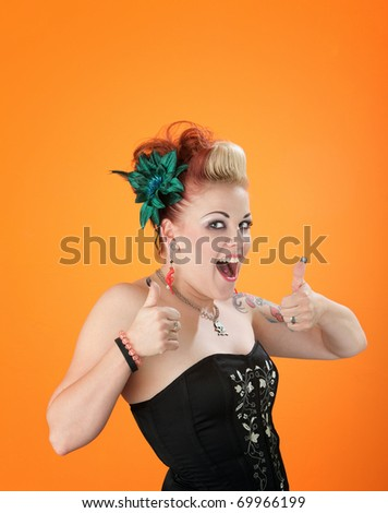 Middle aged, flamboyant lady showing thumbs up on orange background - stock photo