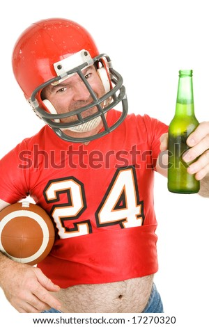 Middle aged football fan wearing his old uniform and having a beer.  White background.