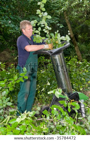 Middle aged forest worker with shredder
