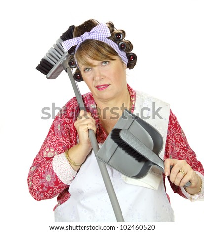Middle aged frumpy house looks forlorn and exasperated holding a dust pan and broom.