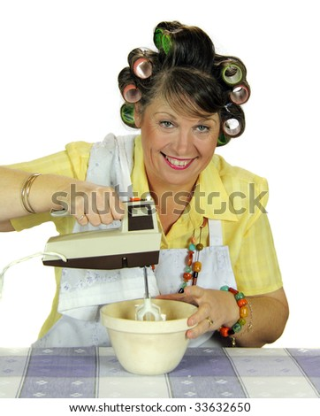 Middle aged frumpy housewife beating eggs with an electric mixer.