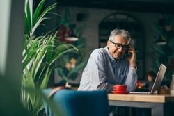 middle aged gray haired man using cellphone in cafe bar