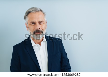 Middle-aged grey-haired man with grey beard, looking at camera. Half-length front bust portrait on plain blue background with copy space