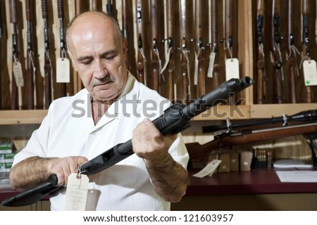 Middle-aged gun shop merchant looking at rifle in store