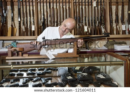 Middle-aged gun shop owner looking at rifle in store