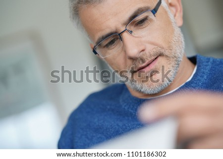 Middle-aged guy with trendy eyeglasses reading newspaper