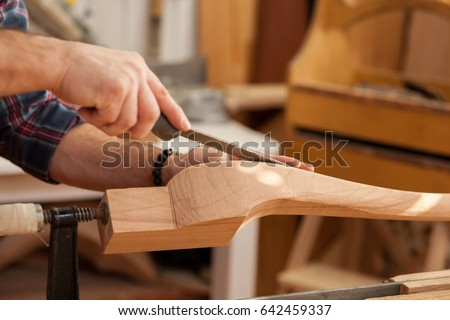 Middle aged handsome carpenter  making final touches to the Cabrioli table (or chair leg)/Carpenter Making Cabrioli Table (or Chair) Legs