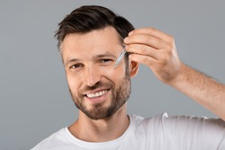 Middle-aged handsome man applying anti-aging serum and smiling at camera over gray studio background, empty space. Handsome cheerful man using nourishing serum for his face, closeup