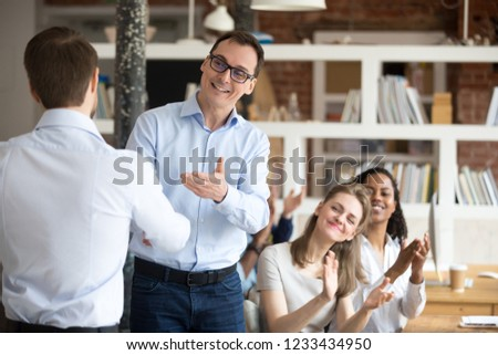 Middle aged happy smiling boss, mentor congratulating employee, praise for good work, new project, idea for startup, shaking hand, welcoming new member of business team, colleagues applauding #1233434950
