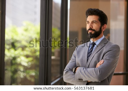 Middle aged Hispanic businessman looks out of office window