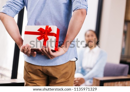 Middle aged husband hiding a surprise gift and roses for surprising his wife on special day such as birthday or wedding anniversary. Celebration and holiday concept #1135971329