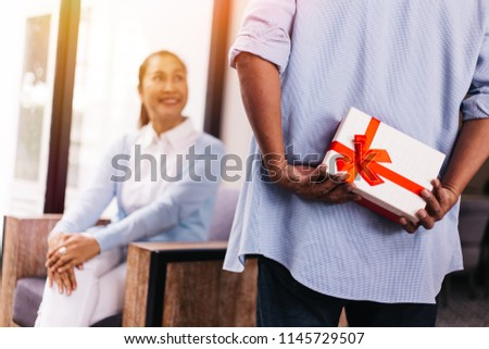 Middle aged husband hiding a surprise gift and roses for surprising his wife on special day such as birthday or wedding anniversary. Celebration and holiday concept #1145729507