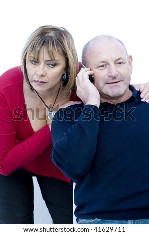 Middle aged husband talking on the phone and wife is listening to the conversation