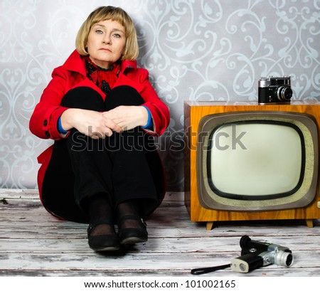 Middle aged lady sitting on old floor next to retro tv and photo camera