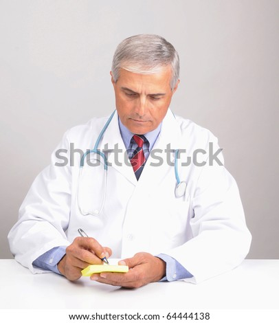 Middle aged male doctor in lab coat with stethoscope writing on a  Prescription Pad