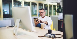 Middle aged male manager watching uploaded photos on tablet sitting at desk with computer photo camera and mug with coffee on break
