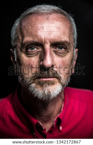Middle aged male portrait headshot with gray hair and beard red shirt on black background and face high contrast to simulate aging or weathered look and age spots