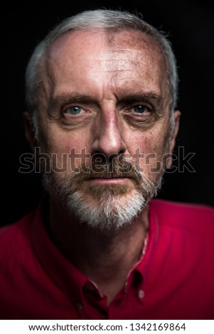 Middle aged male split aging portrait headshot with gray hair and beard red shirt on black background and half face high contrast to simulate aging or weathered look and age spots #1342169864