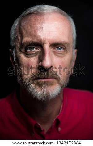 Middle aged male split aging portrait headshot with gray hair and beard red shirt on black background and half face high contrast to simulate aging or weathered look and age spots #1342172864