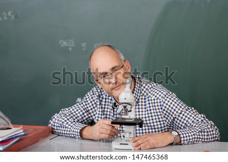 Middle-aged male teacher sitting at his desk in the classroom in front of the blackboard looking at a microscope